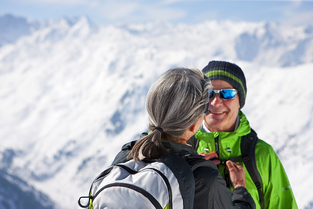 Woman fastening husband's backpack on mountain top