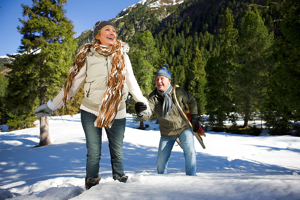 Woman pulling husband uphill in snow