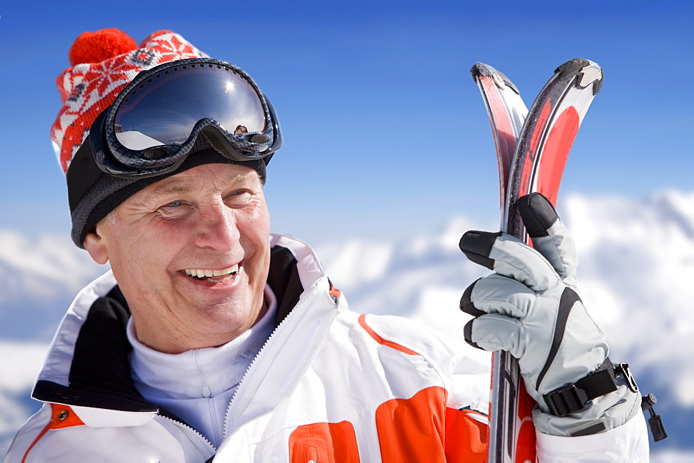 Smiling skier holding skis outdoors