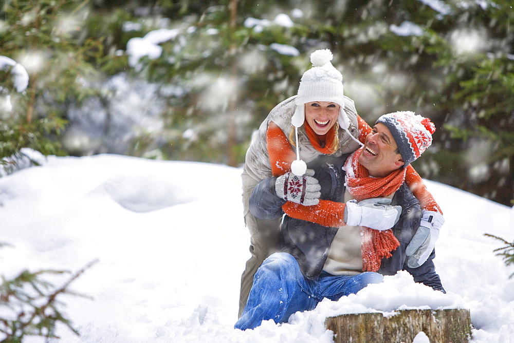 Happy couple playing in snowy woods