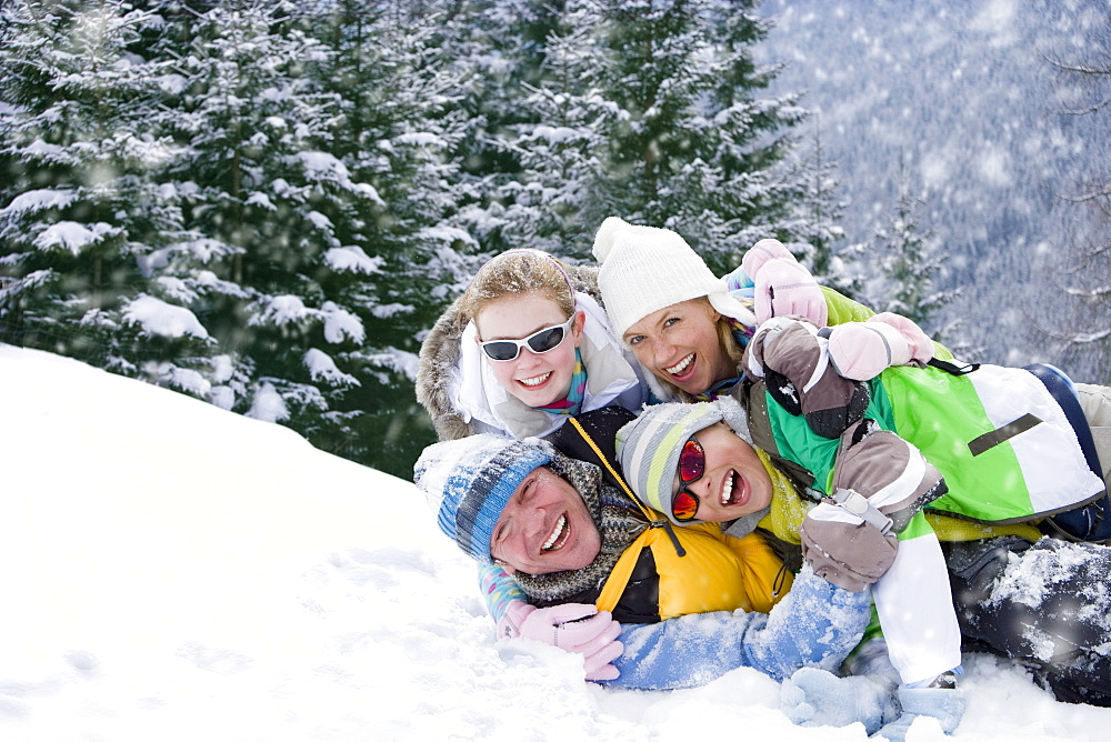 Portrait of smiling family laying in snow