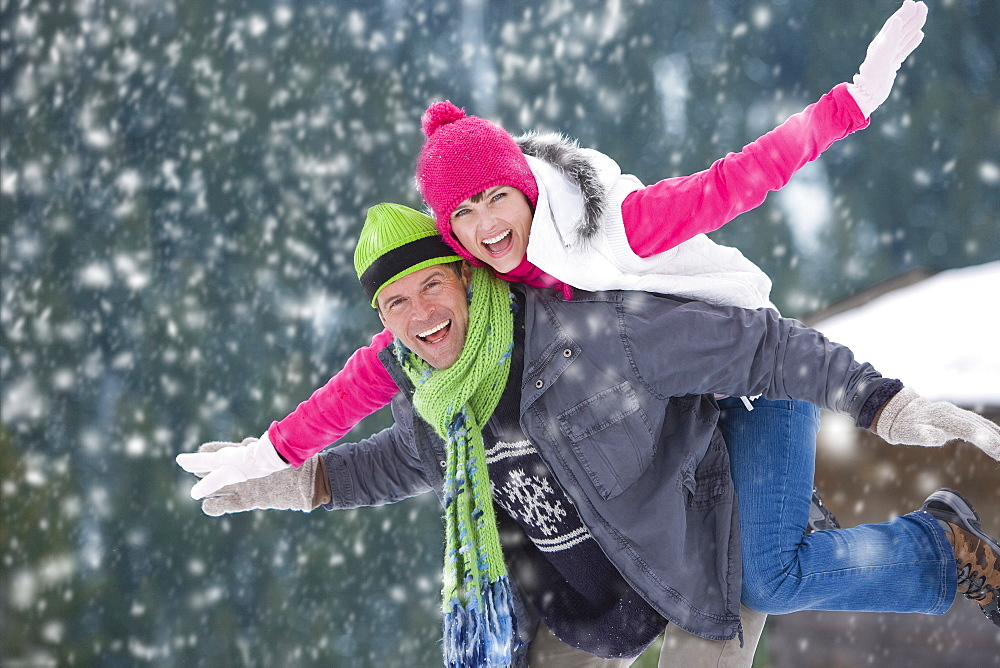 Portrait of man in snow carrying exuberant woman on back