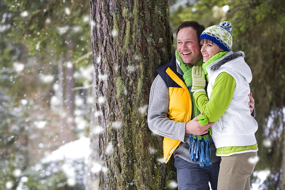 Couple leaning against tree and watching snow fall in woods