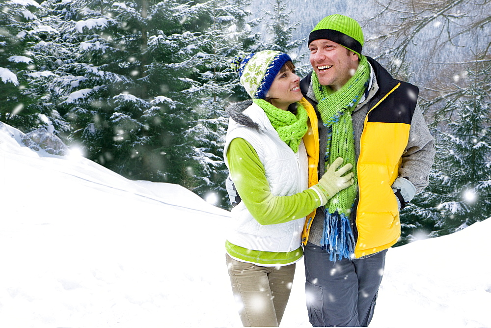 Smiling couple walking in snowy woods