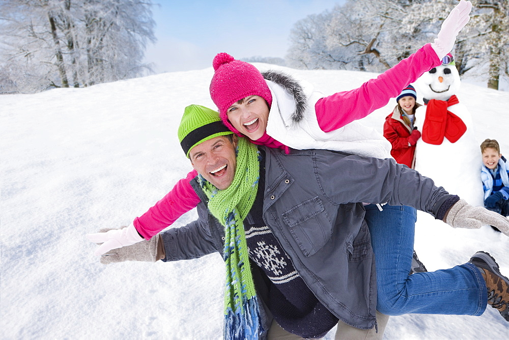 Man carrying exuberant woman on back and children with snowman in background