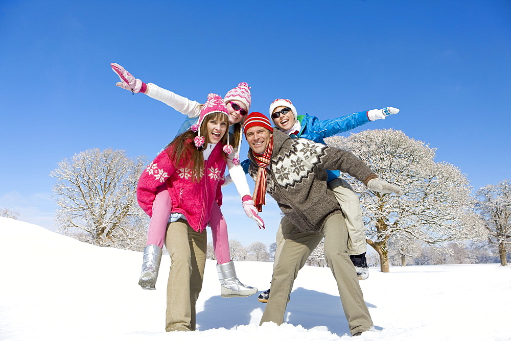 Parents carrying exuberant children on back in sunny, snowy field
