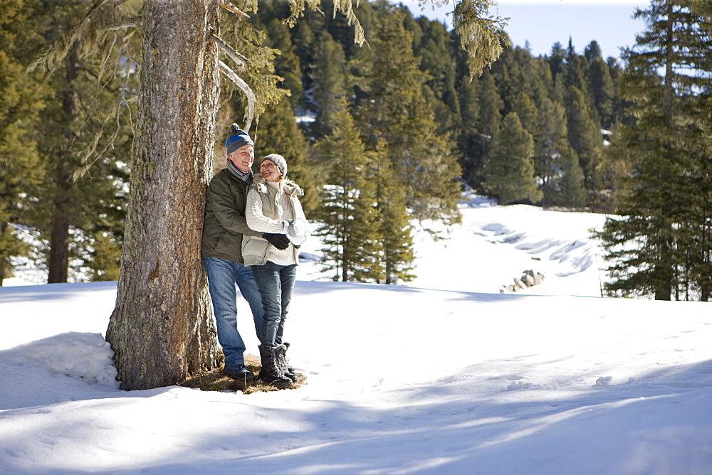 Happy senior couple hugging against tree in snowy woods