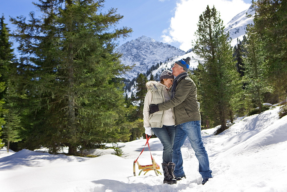 Man kissing woman's forehead in snowy woods