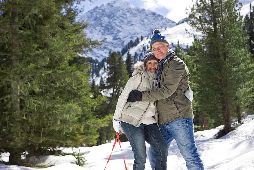 Portrait of happy senior couple hugging in snowy woods