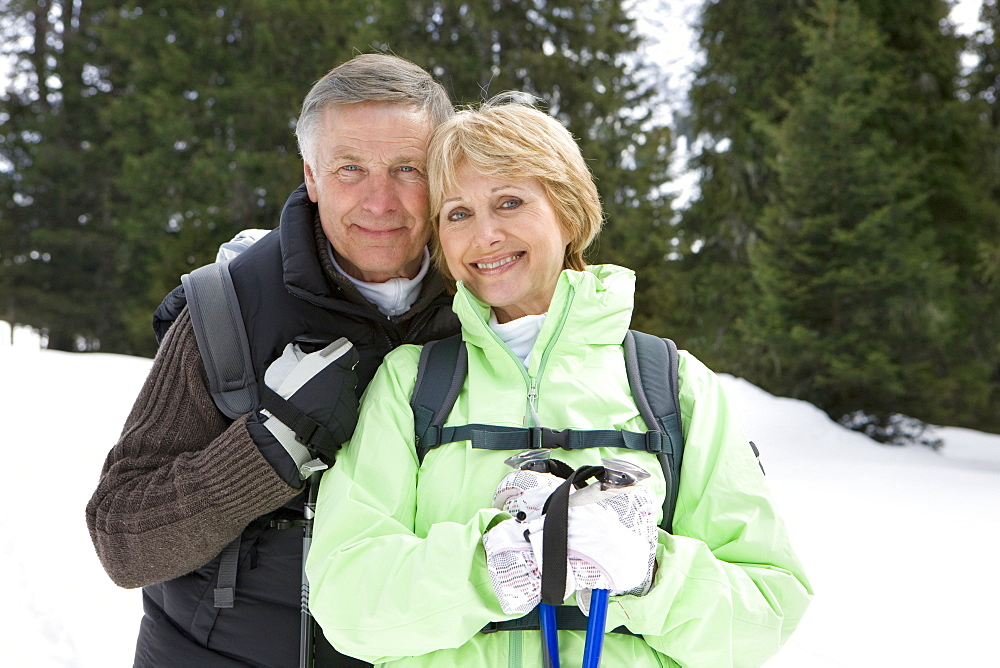 Portrait of happy senior couple in snowy woods