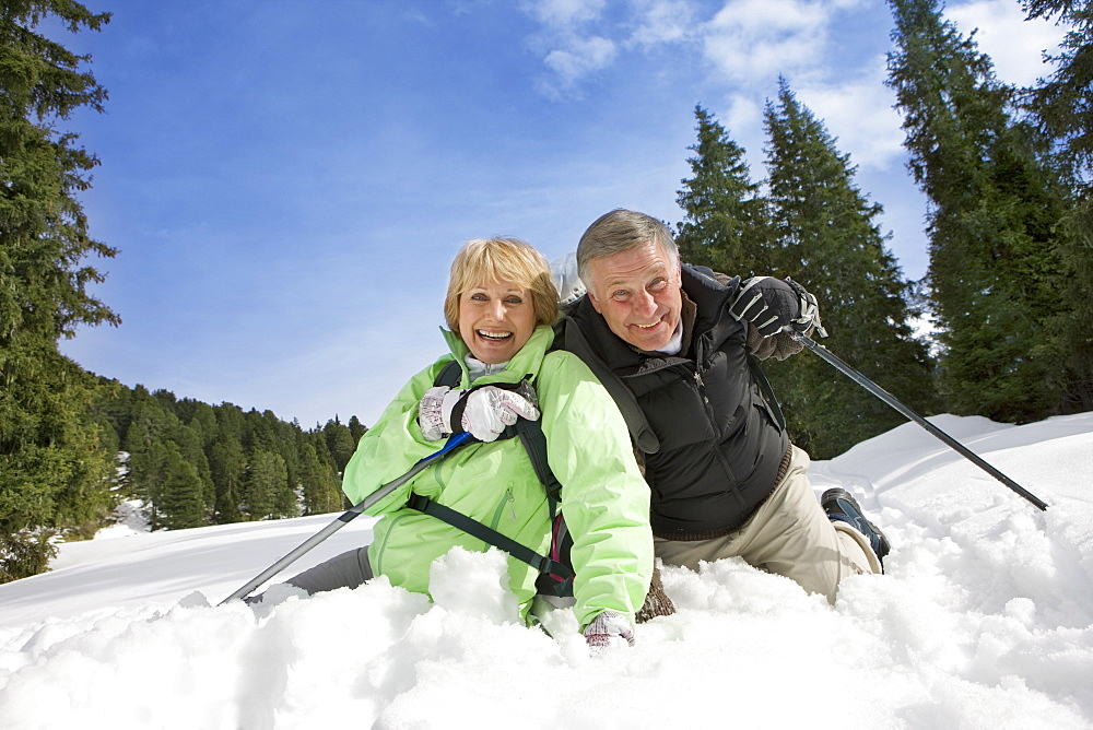 Portrait of happy couple laying in snow with ski poles