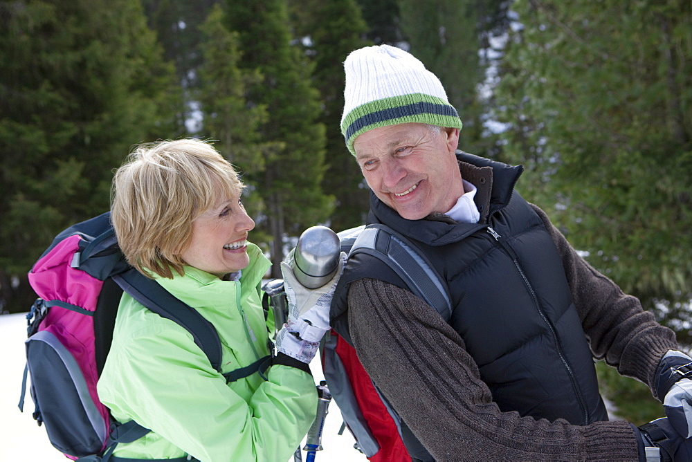 Senior woman in snowy woods placing insulated drink container in man's backpack