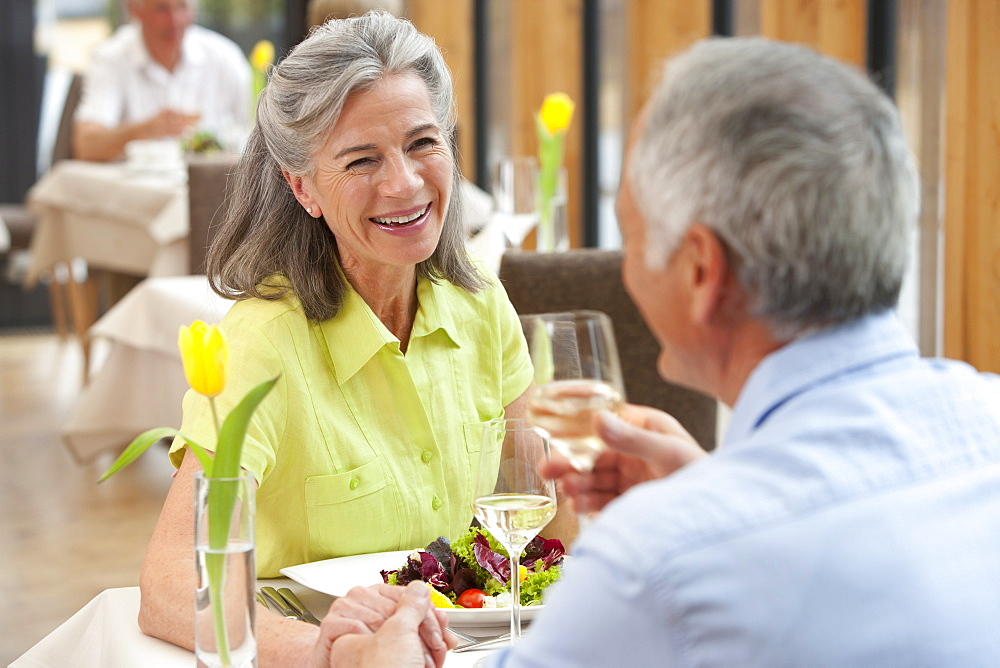 Happy senior couple holding hands and drinking white wine at restaurant table