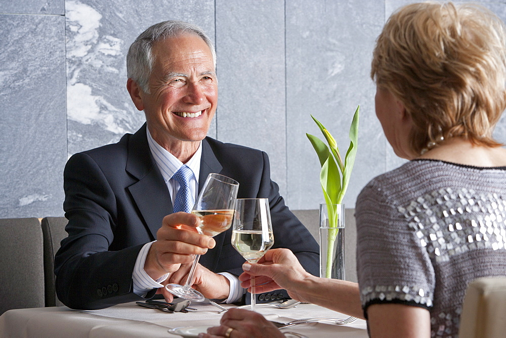 Happy, well-dressed senior couple toasting wine glasses at restaurant table