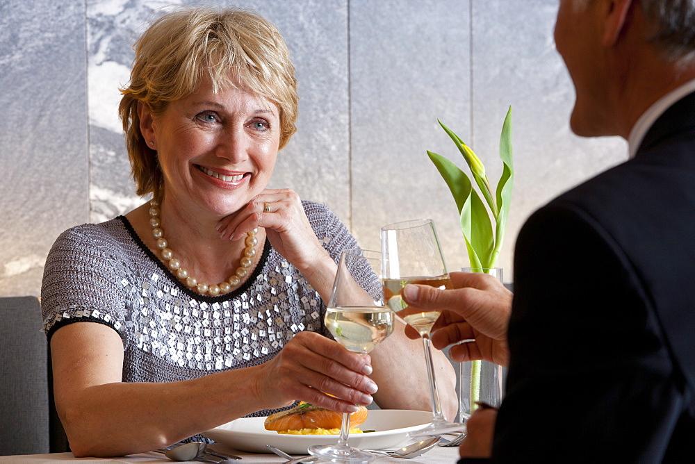Happy well-dressed senior couple toasting wine glasses at restaurant