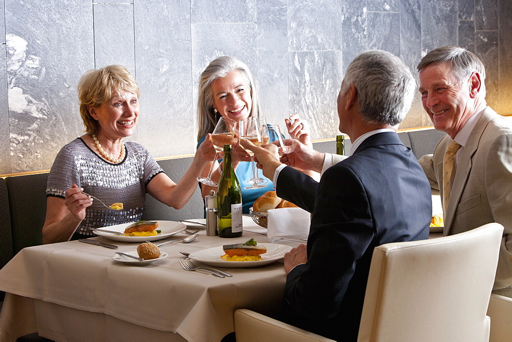 Happy, well-dressed couples toasting wine glasses at restaurant table