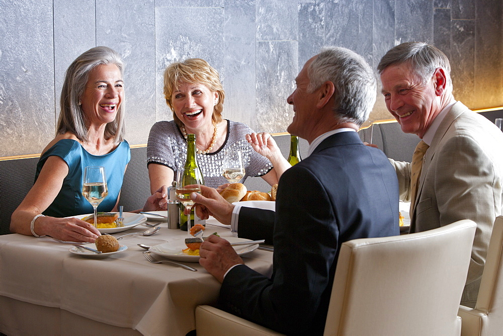 Happy, well-dressed couples dining at restaurant table
