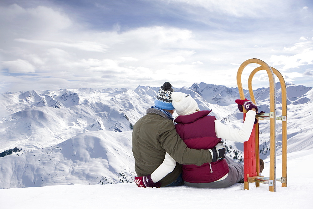 Senior couple with sled sitting and hugging on snowy mountain top
