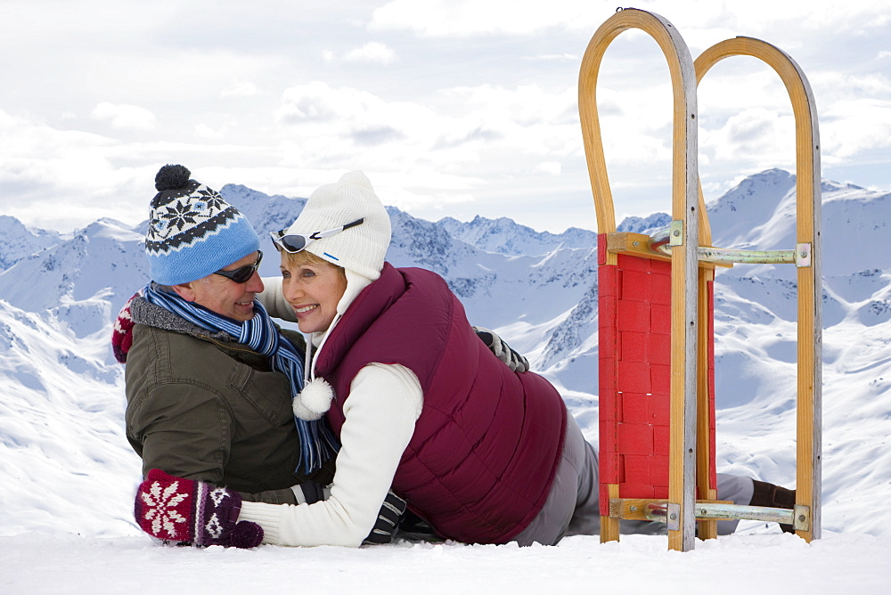 Happy senior couple with sled laying and hugging on snowy mountain top