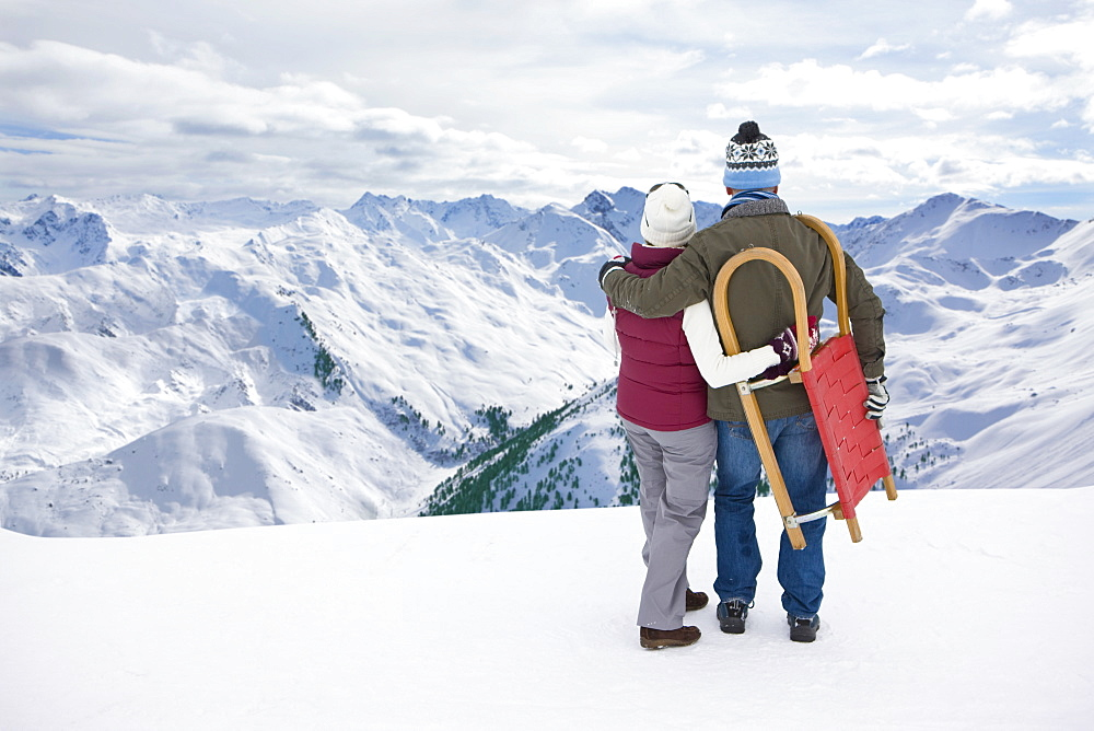 Senior couple with sled hugging on snowy mountain top