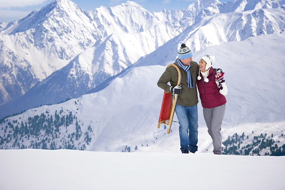 Happy senior couple with sled hugging and walking on snowy mountain