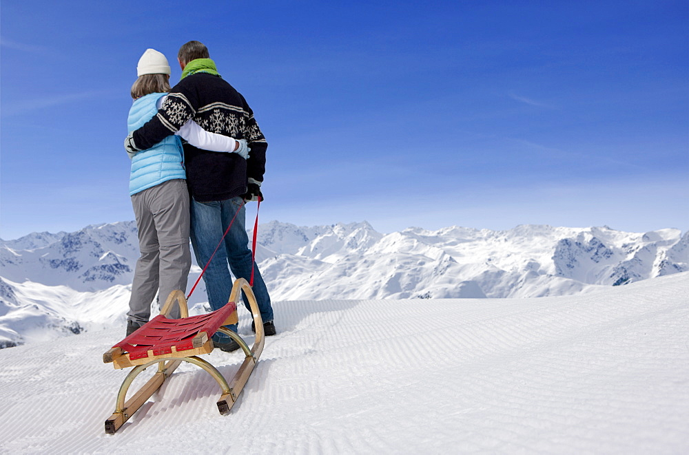 Rear view of couple with sled hugging on snowy mountain