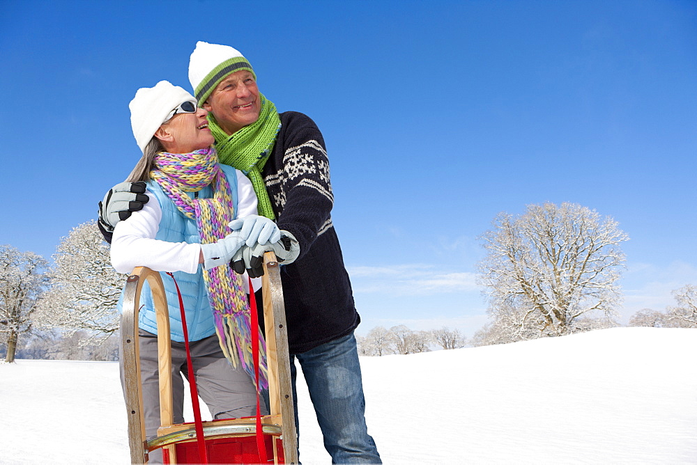 Smiling couple leaning on sled in snowy field