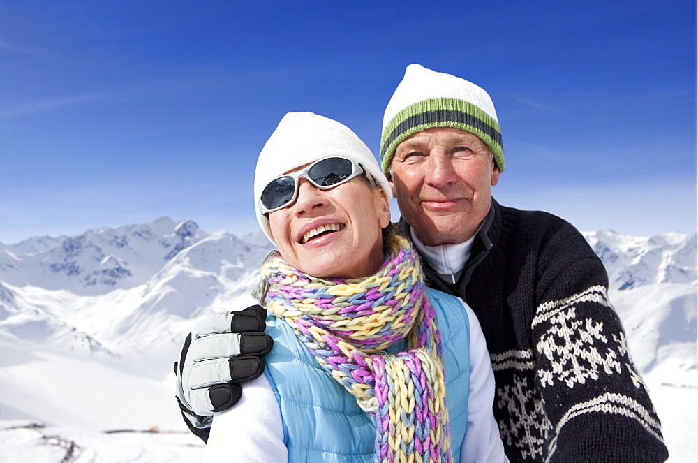 Close up of smiling couple hugging on snowy mountain