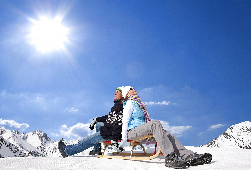 Smiling couple sitting back to back on sled under sun on snowy mountain