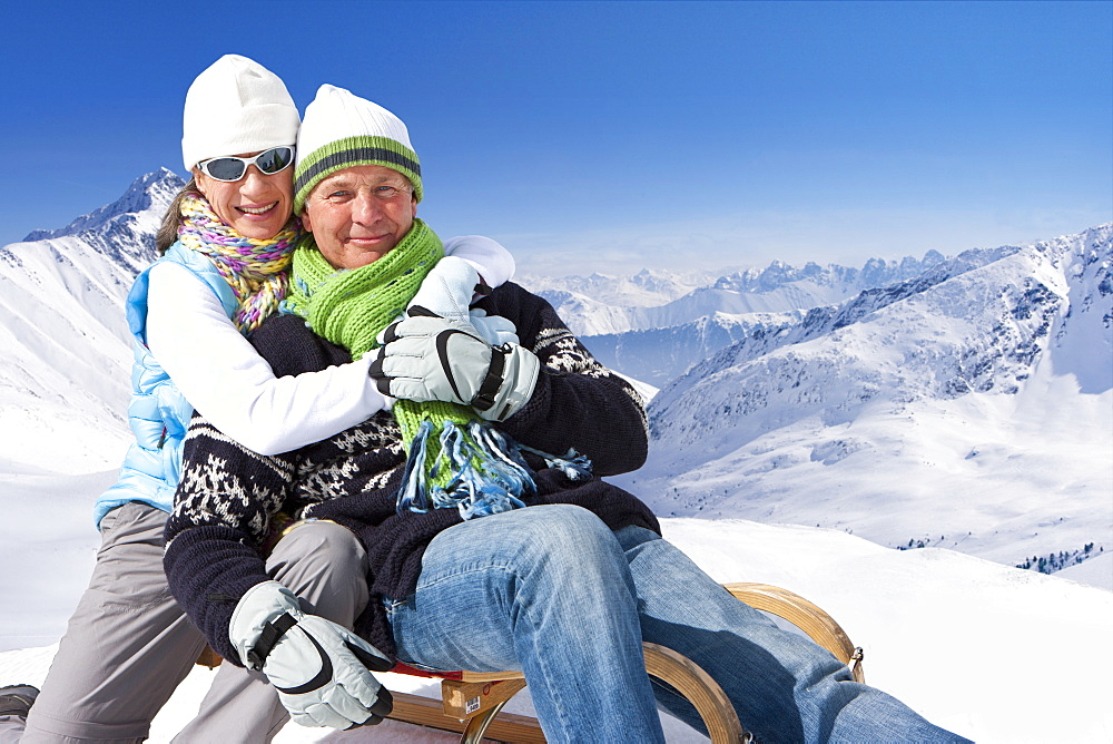 Portrait of smiling couple hugging on sled on snowy mountain