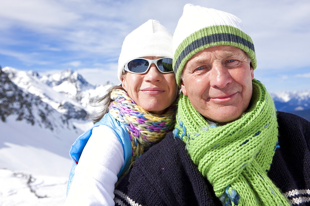 Portrait of smiling couple on snowy mountain