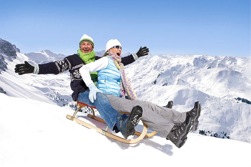 Happy couple sledding down snowy mountain slope