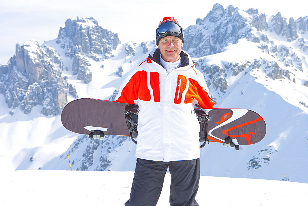 Portrait of smiling senior man with snowboard on snowy mountain
