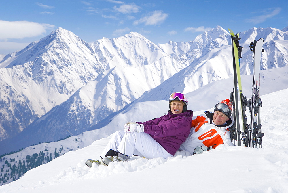 Portrait of smiling senior couple with skis laying on snowy mountain