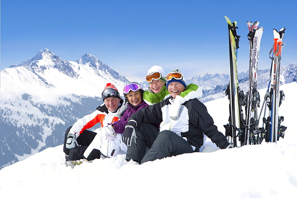 Portrait of smiling senior couples with skis sitting on snowy mountain