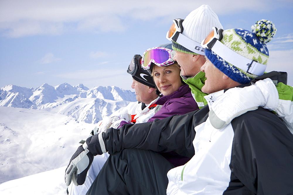 Senior couples sitting on snowy mountain