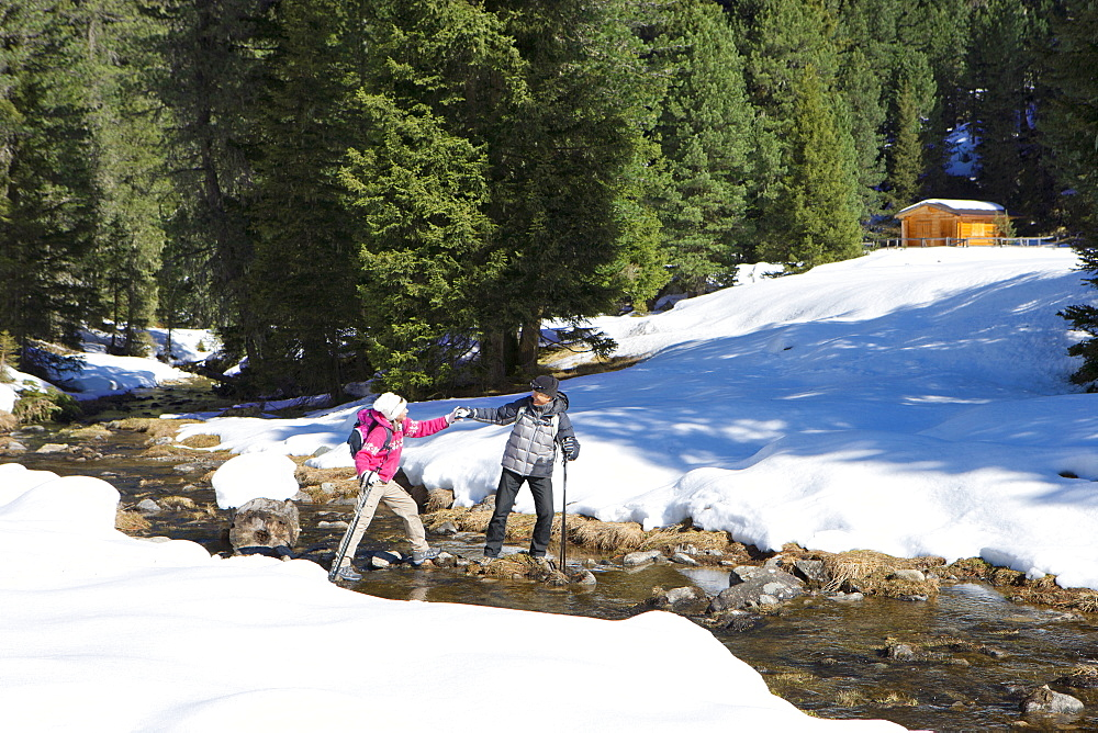 Couple with ski poles crossing stream in snow woods outside cabin