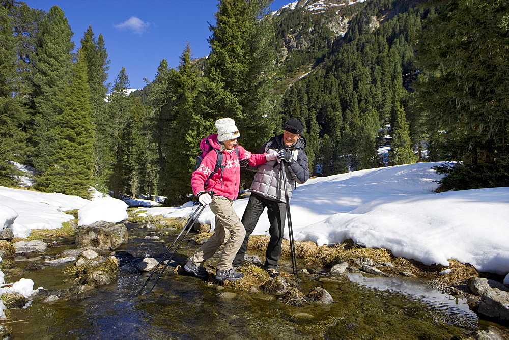 Couple with ski poles crossing stream in snowy woods
