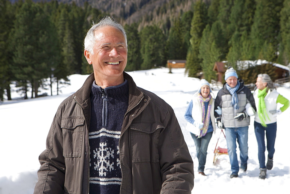 Smiling senior couples in snowy woods outside cabins