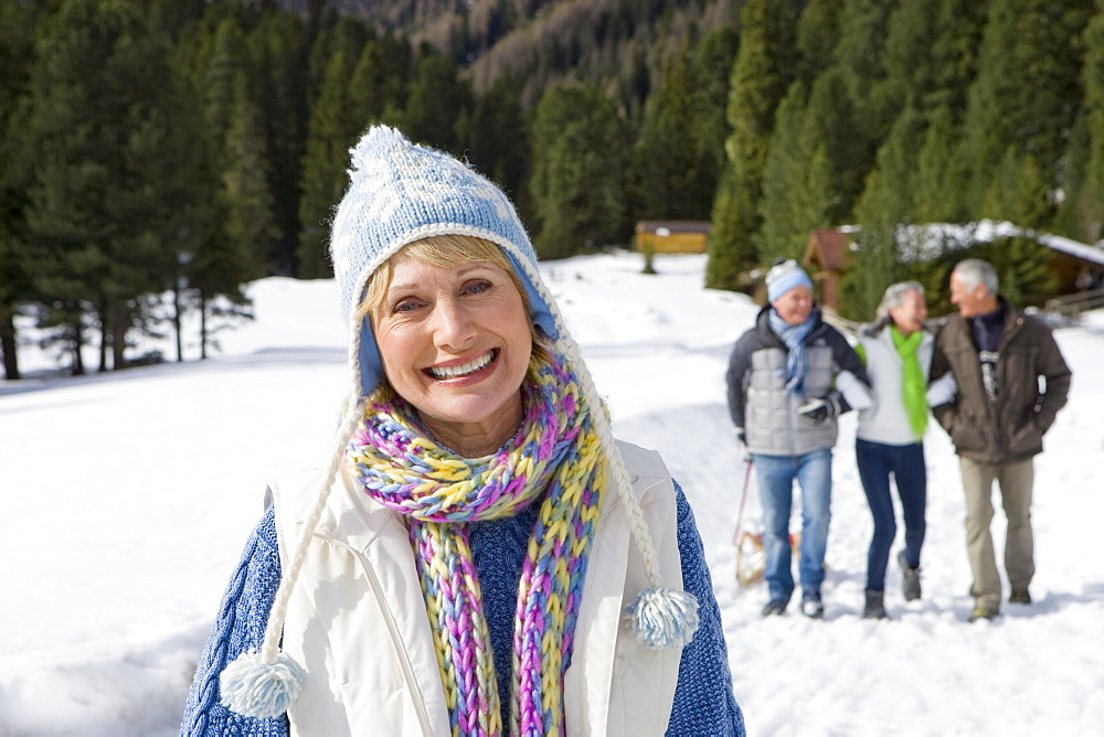 Portrait of smiling senior woman in snowy woods with friends in background