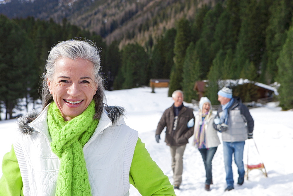Portrait of smiling woman in snowy woods with friends in background