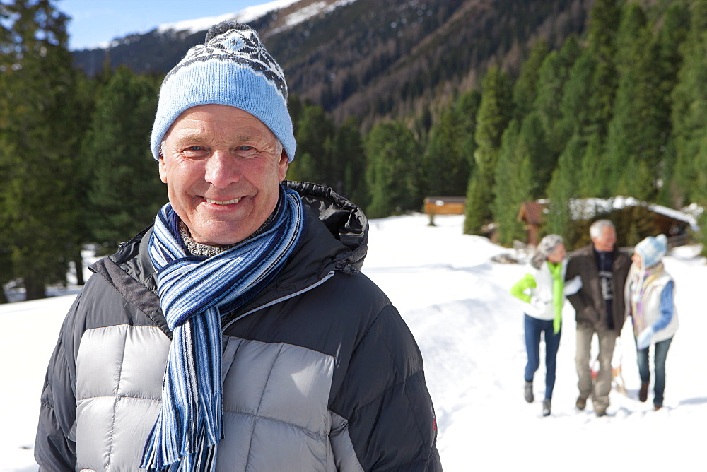 Portrait of smiling senior man in snowy woods with friends in background