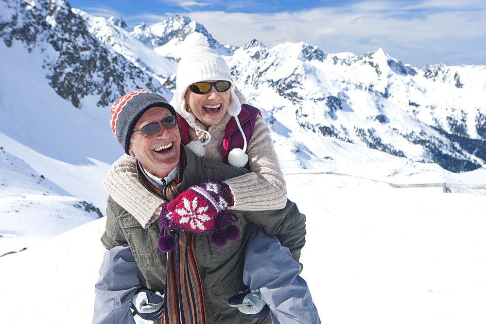 Portrait of smiling senior couple piggybacking on snowy mountain