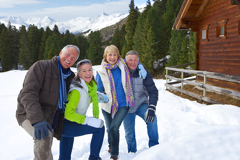Portrait of smiling senior couples outside cabin in snowy woods