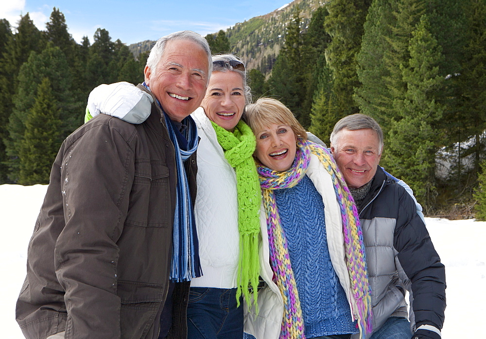 Portrait of smiling senior couples in snowy woods