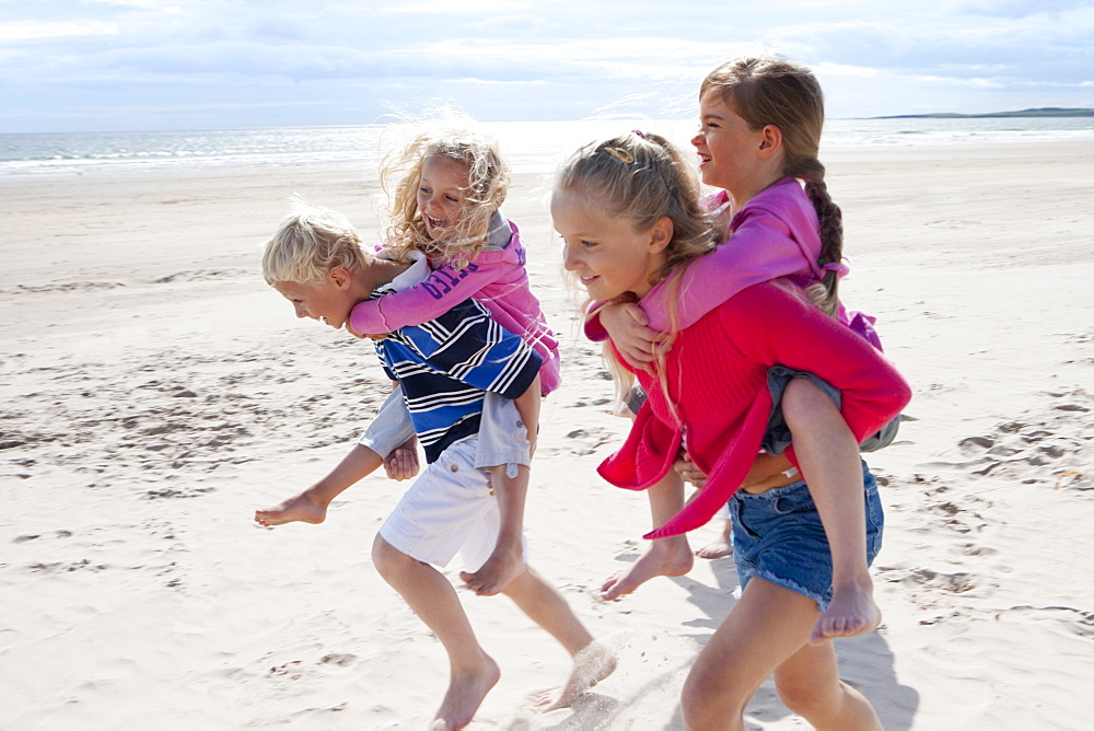 Kids running and piggybacking on sunny beach