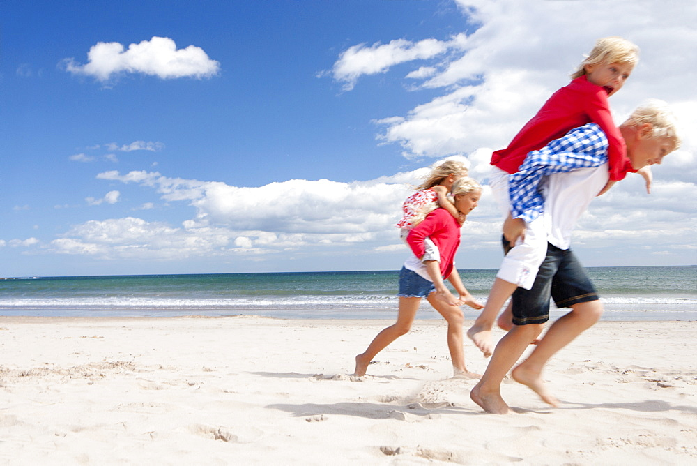 Boy and girls piggybacking on sunny beach
