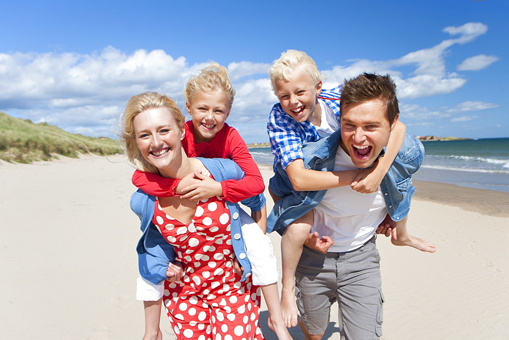 Portrait of smiling parents piggybacking son and daughter on sunny beach