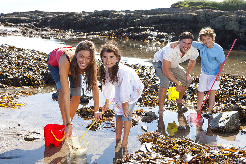 Portrait of smiling family with nets and pails fishing in tide pool