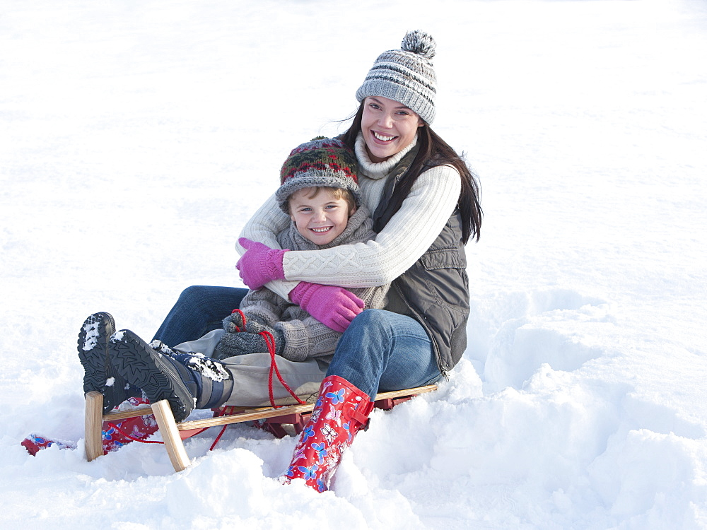 Portrait of smiling mother and son sitting on sled and hugging in snow